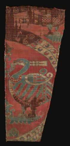 A SILK SAMIT FRAGMENT, SPAIN, CIRCA 1100 of rectangular form, woven with red, cream and blue silk threads with a repeat pattern of large foliate roundels each enclosing paired confronting peacocks supported on a petalled base and flanking a central palmette standard with pearl fringing 40 by 18cm.
