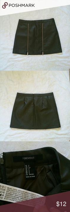 """Dark green faux leather zipper skirt Dark green faux leather skirt from Forever 21. There are 2 zippers in the front. Very slight stretch. There are no rips or stains. Skirt is lined. Zips up in the back.   Measurements: Waist = 26"""" Length = 13.5"""" Forever 21 Skirts"""
