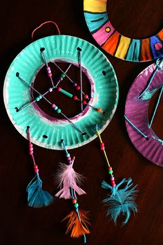 Colourful rings of paper plate, painted bright colours and woven with yarn which has beads strung along it.