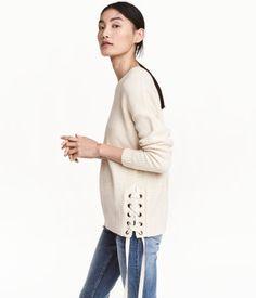 Baumwollpullover mit Schnürung an den Seiten. Modell mit überschnittenen Schultern und Rippenbündchen an Hals, Ärmeln und Saum.