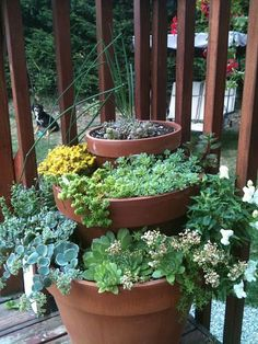 3 pots stacked and filled with different plants