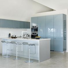 Spacious kitchen with sea-blue cabinetry, central peninsula and stainless steel bar stools Modern Large Kitchens, Grey Kitchens, Home Kitchens, Gloss Kitchen Cabinets, Glossy Kitchen, Kitchen Cupboard Colours, Kitchen Colors, Open Plan Kitchen, New Kitchen