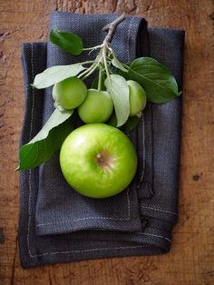 Green apples are vibrant against this stitched navy napkin