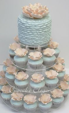 Baby blue and white wedding cupcakes in a gorgeous tower with a layer of cake on top #wedding #weddingcupcakes #cupcaketower #blue #flowers