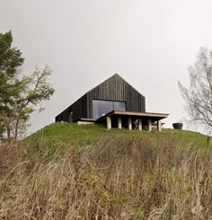 A Rustic Riverfront Farmhouse Design in Latvia by NRJA Architecture:It looks like a modern barn house rather than a compound style house plan. This black house with beveled wall on its entrance was designed by NRJA Architecture. The house was built in a serene surrounding. This modest home design accommodates daily living such as a guest house, sauna, cellar, a volleyball field and football area.