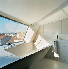 The cavity for the bathtub is part of the same continuous form-world as House Ray sloping roofscape. The white tub is made from Corian; the faucet is by Dornbracht. Photo 5 of 16 in The Penthouse Has Landed. Browse inspirational photos of modern homes. Bad Inspiration, Bathroom Inspiration, Modern Bathroom Design, Modern House Design, Bathroom Interior, Modern Bathtub, Contemporary Design, Futuristic Home, Pent House
