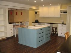Oh. Em. Gee. Dream basement craft room. Cabinets all around, raised cutting table in middle of room, homework space for the kids looking into great room.