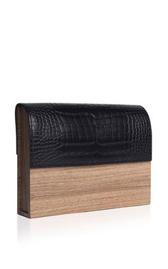 This clutch by **Hugo Matha** is rendered in walnut and matte black alligator and features a structural body, fold over flap and calfskin lining.