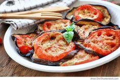 Die Auberginen in 1 cm dicke Scheiben schneiden, mit Salz würzen und für 30 Minuten ziehen lassen. Anschließend die Auberginen im kalten Wasser durchspülen und in eine Auflaufform legen. Den Knoblauch durch die Knoblauchpresse drücken und auf die Auberginenringe gleichmäßig verteilen. Den Käse fein reiben. Die Tomaten ebenfalls in Scheiben schneiden und auf die Auberginen