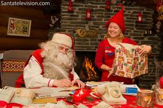 Santa writing letter with a postal elf in Santa Claus Main Post Office in Rovaniemi