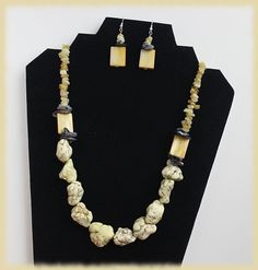 Jewelry set (necklace and earrings) in light yellow gemstones with black shell accents