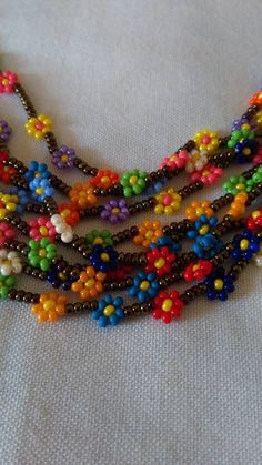 You will love this gorgeous Flower Chain Crochet Pattern and we have included an Easy Video Tutorial for you to try. Check out the ideas now.Colourful Daisy Chain necklace with magnetic clasp.This post was discovered by SeHandmade beaded bracelet and Beaded Flowers Patterns, Beaded Jewelry Patterns, Bracelet Patterns, Beading Patterns, Beading Ideas, Seed Bead Necklace, Seed Bead Jewelry, Bead Jewellery, Flower Necklace