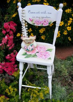 Vintage child's chair with hand-painted shabby roses creates romance in a garden.