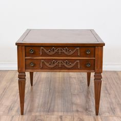 This neoclassical end table is featured in a solid wood with a light cherry finish. This side table is in good condition with tapered legs, 1 drawer and carved floral details. Perfect as a nightstand with storage! #neoclassical #tables #endtable #sandiegovintage #vintagefurniture