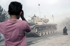 Best photographs of the day: human pyramids and arrowheads in Washington- Karkamış, Turkey  A boy looks at Turkish army tanks and armoured personnel carriers moving toward the Syrian border. The Turkish president, Recep Tayyip Erdoğan, said late on Wednesday that Syrian opposition forces aided by Ankara have taken back the border town of Jarablus from the Islamic State group Photograph: Halit Onur Sandal/AP