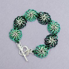 Chrysanthemum weave bracelet using enameled copper in mint and petrol, plus silver-filled rings and toggle.