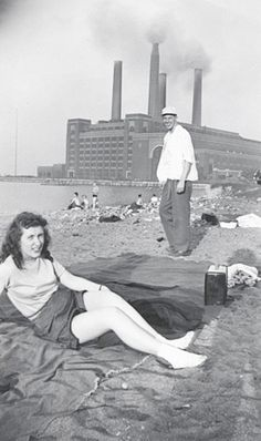 Smiling couple pose on Sunday afternoon riverfront beach with portable radio and blanket as particulate pollution pours from smokestacks of factory or power plant on shore in background. 1950s vernacular photo snapshot - www.reservatory.net
