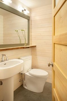 big mirror (giant medicine cabinet?) extends over toilet and sink to make space feel bigger
