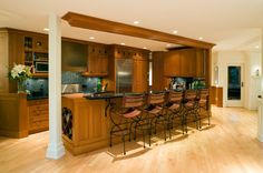 A wooden kitchen with a long eat-in bar and a dusky blue backsplash.
