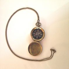 """A compass encased in a brass locket will ensure you will always find your way. Pendant: 1 3/8"""" diameter x 1/2"""" height Chain: 28"""" long"""