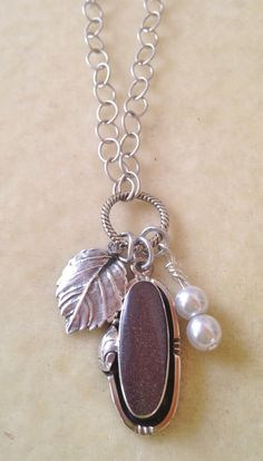 "An embellished silver pendant inlayed with purple goldstone, a silver leaf and two crystal pearls on a twisted jump ring are attached to a brushed silver link chain!   It measures approximately  22"" and is finished with a brushed sliver toggle clasp.  Please note the clasp can be changed to a lobster claw style which would make it adjustable."