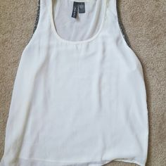 White tank top with black beading detail Fun and Flirt tank top with black beading detail around the arms. The back is sheer. Perfect for mixing and matching this summer! Beading a little loose in armpit as shown in picture 4. Fun & Flirt Tops Tank Tops