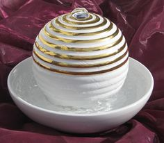 Dieser Feng Shui Brunnen stammt wieder aus der Hand von Brigitte Kustermann. Die Schale ist tief und kann viel Wasser aufnehmen. 9 goldenen Ringe symbolisieren immerwährenden Wohlstand auf allen Ebenen.  Die weiße Glasur ist sehr robust und passt ausgezeichnet in ein helles, klares Wohnambiente. Höhe 18 cm, Durchmesser 25 cm #fengshui #brunnen #deko