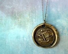 A pendant like you might find in a pirate's treasure, marked by a ship under sail.