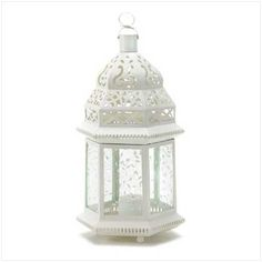 Large White Moroccan Lantern.  Light leaps in lacy patterns from the cutwork roof and vine-patterned panels of this alluring candle lamp.    Cast a glamorous aura over an outdoor gathering, or use several together to elegantly illuminate a shadowy garden path!