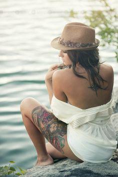 Pequeño tatuaje de una rosa de los vientos con los puntos cardinales en la parte alta de la espalda.