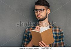 What shall I write?Pensive young man in sunglasses holding notebook and looking away while standing against grey background - stock photo