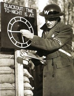 An air-raid warden sets a black-out time clock indicator at an A.R.P. post near London - 1 November 1939