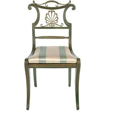 Regency Side Chair- These Regency brass-mounted, painted and parcel-gilt dining chairs are early 19th Century. Available in side and arm chair versions; each arm chair has scrolled cresting surmounted by a foliate cast, scrolled handle above a brass palmette and a twisted horizontal slat. The downward scrolled arms center a trapezoidal seat which is raised on saber legs.    The original set of four arm and two side chairs is in the collection of Mr. and Mrs. Gordon Getty, San Francisco.