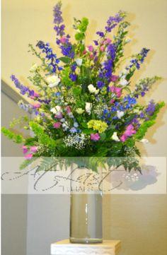 Tall Wedding arrangement of blue delphenium, bells of ireland, purple, green and white flowers