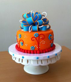 Orange and Blue Birthday Cake - This is an 8 inch mimosa cake with citrus buttercream. This design came directly from a beautiful two tier cake by Jaime3679. When my friend asked me to do something with blue and orange I was so excited because I had saved her cake a while back because I thought the colors and styling were awesome. I chose to do a different topper because it was a single tier and I wanted something over the top. I used the new wilton fondant molds for the flowers. They were…