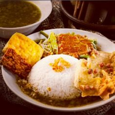 Nasi pecel rawon, is a strong rich traditional Indonesian beef black soup that uses black nuts(keluak) served w/ rice.