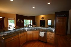 Kitchen remodel with a kitchen island breakfast bar, oak flooring, and entertainment niche.