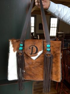 A hair on hide Buckaroo Tote, with exterior side pockets lined in suede, turquoise stones and a D for Danielle. gowestdesigns.us