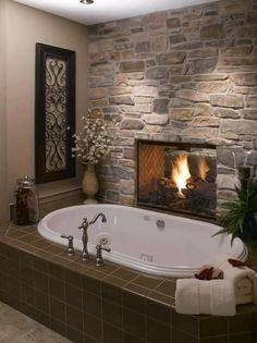 Fireside bathtub with stone accent wall. So cool!