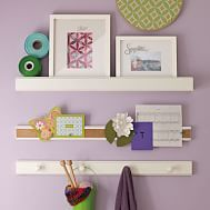 Display and organize pictures, awards and more with these modular rails in a variety of mix-and-match functions. The ledge holds framed certificates or photos, the corkboard rail lets you pin up postcards, and the peg rail is perfect for hanging ribbons, necklaces and other essentials.