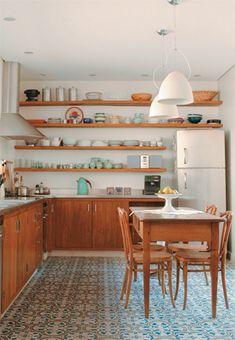 Nesta cozinha, decorada pelas arquitetas Carolina Maluhy e Isis Chaulon, o ladrilho azul e amarelo conversa com o tom da madeira.