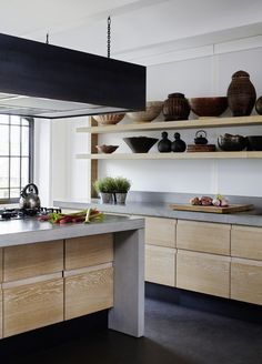 dark floors with wood cabinets and concrete counters.