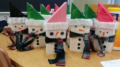 """Snowmen parent holiday gift. Made of 2x4 wood cut 9"""" at the tip and 6"""" at the low corner. My 1st graders painted them with tempera paints (I did one coat but would recommend two), then hot glue gunned googly eyes, buttons, a flannel nose, and the fur lining on the hat. Finish by tying on a strip of fleece. My sister made one as a gift to my mom 15 years ago. Happy to resurrect this one for parents of my students to love for years to come!"""