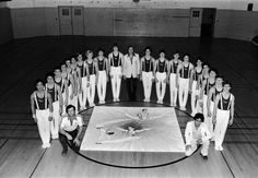 Black and white photo of the 1980 University of Oregon men's gymnastics team taken in an Esslinger Hall gym. Head coach Bill Ballester is standing at center. ©University of Oregon Libraries - Special Collections and University Archives