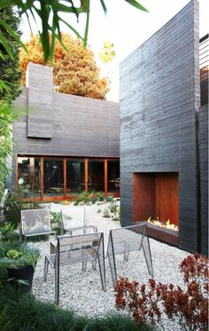 7 Homes With Amazing Fire Pits via @mydomaineWe love this modern, cabin-like abode in Venice, California. The blackened wood siding coupled with copper-hued accents and scrubby plantings create a unique setting. The oversize fireplace is stunning. We particularly love the contrast created by keeping the fire itself low to the ground while its chimney and walls rise to great heights above. blackened wood siding coupled with cooper hued accents and scrubby plantings