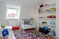 Das weiße Bett im Kinderzimmer mit dem bunten Teppich