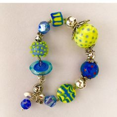 Lemon  yellow and periwinkle glass make this large hollow glass beads bracelet. Pewter and sterling silver accents. Magnet claps. Comes in a handcrafted wooden gift box