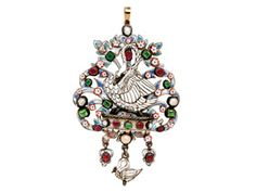 A Renaissance Revival Enamel and Gem-set Pendant Necklace  The openwork plaque designed with a white enamel swan and cygnet amid white and blue enamel foliage, and suspending the baby swan between ruby drops, accented with rubies, emeralds, and split pearls mounted in silver, mid 19th century, from a 14k gold curb linking chain.