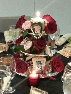Vintage centerpiece with roses, pearls,  burlap ribbon, candle, jeweled butterfies, and picture frames on a tired serving tray.