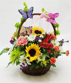Mom's Butterfly Basket - Our Natural Garden Ten Inch Basket is Designed with Fresh Garden Flowers including Yellow Sunflowers, Green Fuji Chrysanthemums, Lilies and Statice Accented with Two Butterflies on the Handle.